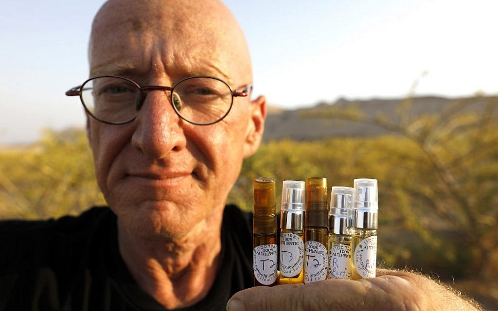 Farmer Guy Erlich shows ampules of scented oils extracted from plants and trees at a farm on a small hill near the settlement of Almog in the West Bank, on May 28, 2019 (MENAHEM KAHANA / AFP)
