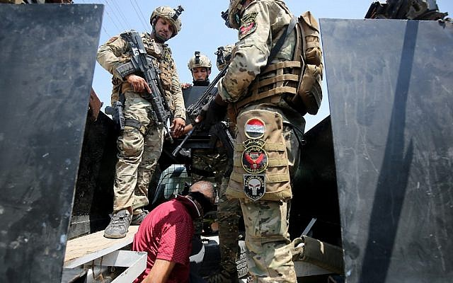 Iraq's rapid response forces detain a man as they storm a house in the Tarmiyah district, north of Baghdad, searching for wanted Islamic State group suspects on July 21, 2019. (AHMAD AL-RUBAYE / AFP)