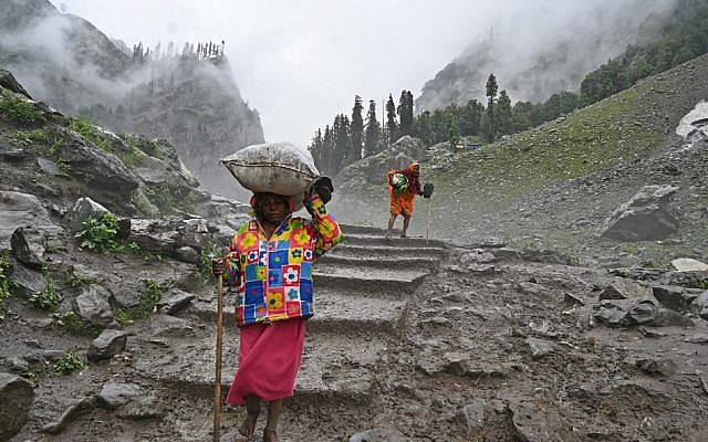 Indian Hindu pilgrims carry bags on their head as they trek up to Chandanwari in Kashmir, some 115 km southeast of Srinagar, during the annual Hindu pilgrimage on July 27, 2019 to the holy cave shrine of Amarnath. (TAUSEEF MUSTAFA / AFP)