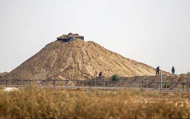 Illustrative: A picture taken from Khan Younis in the southern Gaza Strip shows Israeli soldiers inspecting the area around their observation post next to the border fence with the coastal enclave on August 1, 2019, following a firefight with a Palestinian gunman. (Said Khatib/AFP)