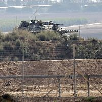 A picture taken from Khan Younis in the southern Gaza Strip shows an Israeli tank near the border fence with the coastal enclave on August 1, 2019, following a firefight with a Palestinian gunman. (Said Khatib/AFP)