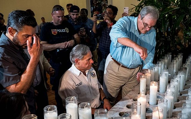 Texas Governor Greg Abbott (C) and El Paso Mayor Dee Margo (R) light candles after a vigil ceremony at Saint Pius X Church, following a deadly mass shooting, in El Paso, Texas, August 3, 2019 (Joel Angel JUAREZ / AFP)