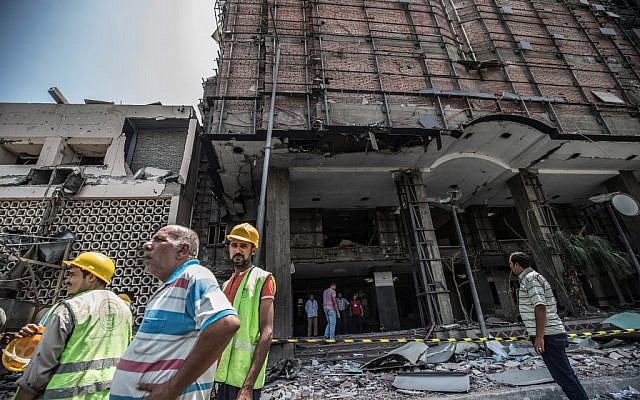 Egyptians walk outside the National Cancer Institute in the capital Cairo on August 5, 2019, the morning after a car bombing. (Khaled Desouki/AFP)