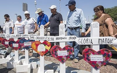 People pray beside crosses with the names of victims who died in the shooting to a makeshift memorial after the shooting that left 22 people dead at the Cielo Vista Mall WalMart in El Paso, Texas, on August 5, 2019. (Mark Ralston/AFP)