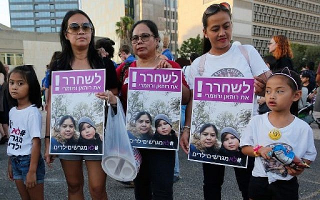 "Filipino children and their mothers carry a banner which reads in Hebrew  ""release Rohan and Rosemarie "" during a protest against deportation in Tel Aviv on August 6, 2019. (Photo by Gil COHEN-MAGEN / AFP)"
