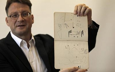 National Library archival expert and Humanities Collection Curator Stefan Litt shows drawings by novelist Franz Kafka, during a press conference in the National Library of Israel in Jerusalem, on August 7, 2019. Hundreds of letters, manuscripts, journals, notebooks, sketches and more - handwritten by Brod and Kafka - have been transferred to the National Library of Israel, following orders by Israeli and Swiss courts to open vaults in Zurich, which had stored the materials for decades. These materials, part of Max Brod's literary estate, have now been returned to Israel and have arrived at the National Library in Jerusalem, in accordance with Brod's wishes. (Menahem Kahana / AFP)