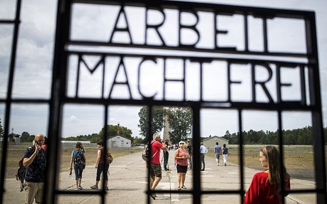"Visitors are seen through an iron gate carrying the German phrase ""Arbeit Macht Frei"" (work sets you free) at the former concentration camp in Oranienburg, eastern Germany on August 7, 2019. (Odd Andersen/AFP)"