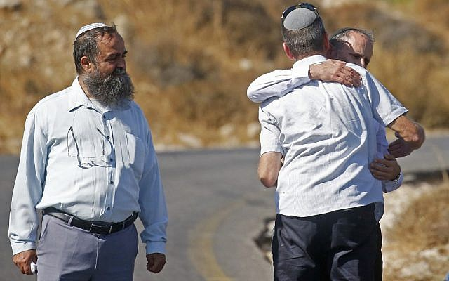 Israelis embrace next to the scene where Dvir Sorek was found stabbed to death, outside the West Bank settlement of Migdal Oz, on August 8, 2019. (Hazem Bader/AFP)