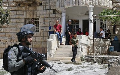 Palestinians look on as Israeli soldiers take part in a house-to-house search operation in the West Bank village of Beit Fajjar near Bethlehem on August 8, 2019, following a stabbing attack. (HAZEM BADER / AFP)