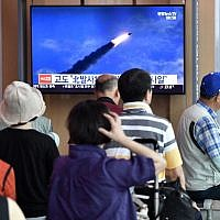 People watch a television news screen showing file footage of North Korea's missile launch, at a railway station in Seoul on August 10, 2019. (Jung Yeon-je / AFP)