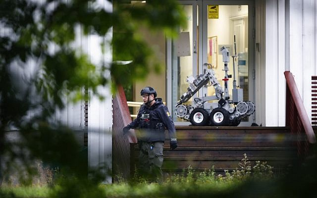 A Norwegian cop walks past a robot in front of the al-Noor Islamic Center mosque, where a gunman armed with multiple weapons went on a shooting spree in the Oslo suburb of Baerum on August 10, 2019. (Terje Pedersen/NTB Scanpix/AFP)