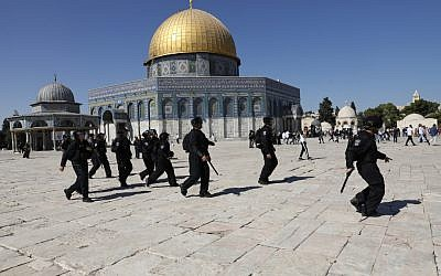 Israeli security forces walk past the Dome of the Rock shrine, as they arrive at the Temple Mount compound in the Old City of Jerusalem on August 11, 2019, after clashes broke out during the overlapping Jewish and Muslim holidays of Eid al-Adha and Tisha B'Av. (Ahmad Gharabli/AFP)