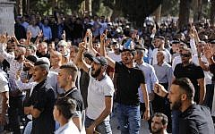 Illustrative: Palestinian Muslims shout at Israeli security forces (unseen) in the Temple Mount in the Old City of Jerusalem on August 11, 2019. (Ahmad Gharabli/AFP)