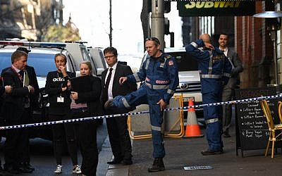 Police gather at the crime scene after a man stabbed a woman and attempted to stab others in central Sydney on August 13, 2019, before being pinned down by members of the public and detained by police. (Photo by Saeed KHAN / AFP)