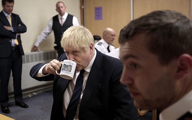 Britain's Prime Minister Boris Johnson (C) drinks from a HMP Leeds mug as he talks with prison staff during a visit to HM Prison Leeds, a Category B men's prison in Leeds, northern England, on August 13, 2019. (Jon Super / POOL / AFP)