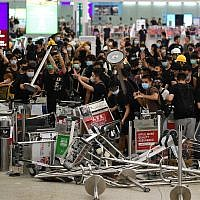 Pro-democracy protestors block the entrance to the airport terminals after a scuffle with police at Hong Kong's international airport late on August 13, 2019. (Manan VATSYAYANA / AFP)