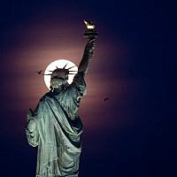 """In this file photo taken on May 18, 2019 the full moon rises behind the Statue of Liberty in New York City. - Acting US immigration chief Ken Cuccinelli came under fire August 13, 2019, for twisting the words of a famed poem that appears on a plaque at the Statue of Liberty. """"Give me your tired and your poor who can stand on their own two feet and who will not become a public charge,"""" Cuccinelli said on National Public Radio when asked if Emma Lazarus' """"The New Colossus"""" is """"part of the American ethos."""" (Photo by Johannes EISELE / AFP)"""