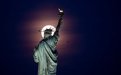 A full moon rises behind the Statue of Liberty in New York City, on May 18, 2019.  (Photo by Johannes EISELE / AFP)