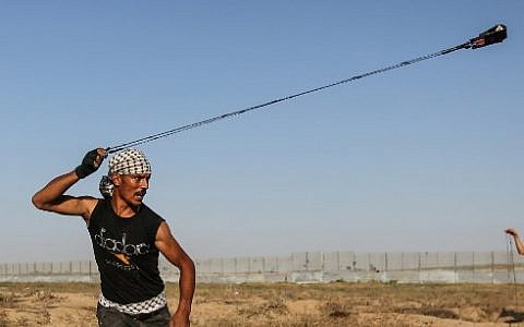 A Palestinian rioter uses a slingshot to hurl stones at Israeli forces near the fence along the border with Israel in the eastern Gaza Strip on August 16, 2019. (Photo by MAHMUD HAMS / AFP)