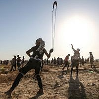 A Palestinian uses a slingshot to hurl stones during clashes with Israeli forces near the border with Israel in the eastern Gaza Strip on August 16, 2019. (MAHMUD HAMS / AFP)
