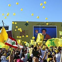 Supporters of the Hezbollah terror group wave the group's flag during a commemoration marking the 13th anniversary of the end of the 2006 war with Israel in the southern Lebanese town of Bint Jbeil on August 16, 2019. (Mahmoud Zayyat/AFP)