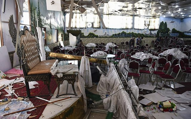 Afghan men investigate in a wedding hall after a deadly bomb blast in Kabul on August 18, 2019. (Wakil Kohsar/AFP)