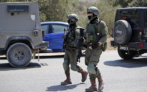 Israeli soldiers stand at the site where a bomb exploded near the Israeli settlement of Dolev in the West Bank on August 23, 2019, killing a teenage Israeli girl and seriously injuring two other people (Ahmad GHARABLI / AFP)