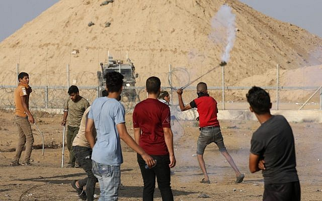 A Palestinian hurls a teargas canister back at Israeli soldiers during clashes along the border fence between the Gaza Strip and Israel, east of the southern Gaza city of Khan Younis, on August 23, 2019. (Said Khatib/AFP)