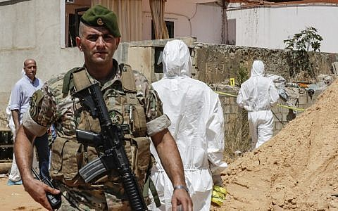A Lebanese army soldier walks past military intelligence forensic investigators inspecting the scene where two drones came down in the vicinity of a media center of Hezbollah terror group earlier in the day, in the south of the capital Beirut, on August 25, 2019. (Anwar Amro/AFP)