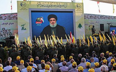 Sympathizers of the Shiite Hezbollah terror group gather to watch the transmission on a large screen of a speech by the movement's leader Hasan Nasrallah, in the town of Al-Ain in Lebanon's Bekaa valley on August 25, 2019. (AFP)