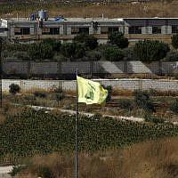 A picture taken on August 26, 2019, near the northern Israeli moshav of Avivim shows a Hezbollah flag in the Lebanon village of Aitaroun. (Jalaa Marey/AFP)