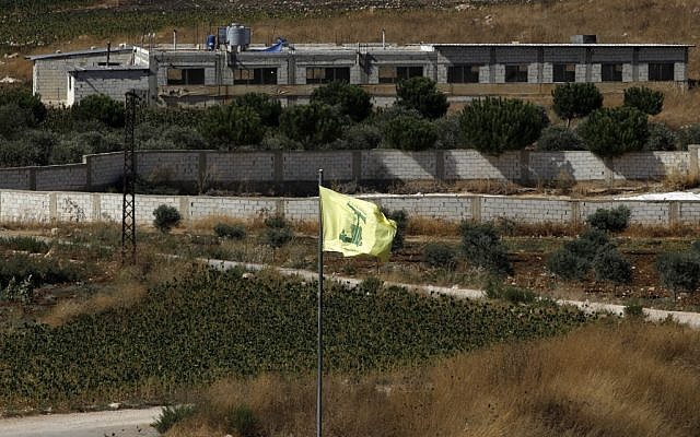 A picture taken on August 26, 2019, near the northern Israeli moshav of Avivim shows a Hezbollah flag in the Lebanon village of Aitaroun. (Jalaa Marey/AFP)