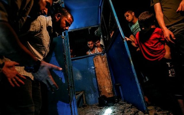 Palestinians look at the destroyed booth of a police checkpoint hit in an explosion in Gaza City on August 27, 2019. (Photo by MAHMUD HAMS / AFP)