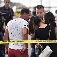 A witness (R) is comforted by friends in Villeurbanne on the outskirts of Lyon, south-eastern France on August 31, 2019, after a knife attack which has left one dead and nine injured. (Photo by PHILIPPE DESMAZES / AFP)