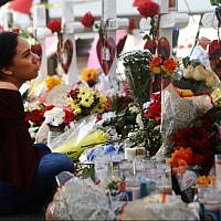 Yamileth Lopez with a photo of her deceased friend Javier Amir Rodriguez at a makeshift memorial for victims of a mass shooting which left at least 22 people dead, on August 6, 2019 in El Paso, Texas. Mario Tama/Getty Images/AFP