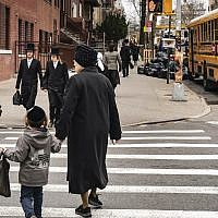 Pedestrians walk past a yeshiva in the South Williamsburg neighborhood of Brooklyn, April 9, 2019. (Drew Angerer/Getty Images via JTA)