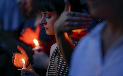 Mourners bow their heads in prayer as they gather for a vigil at the scene of a mass shooting on Sunday, August 4, 2019, in Dayton, Ohio. (AP Photo/John Minchillo)