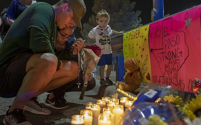Rene Aguilar and Jackie Flores pray at a makeshift memorial for the victims of a mass shooting at a shopping complex in El Paso, Texas, August 4, 2019. (AP Photo/Andres Leighton)