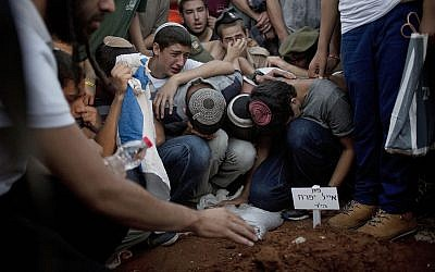 In this July 1, 2014 file photo, family and friends of three Israeli teenagers who were abducted and killed mourn over the grave of Eyal Yifrah, during their funeral in Modi'in. (AP Photo/Ariel Schalit, File)