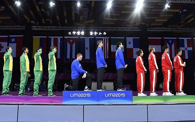 In this August 9, 2019 photo, released by Lima 2019 News Services, Race Imboden of the United States takes a knee, as teammates Mick Itkin and Gerek Meinhardt stand on the podium after winning the gold medal in team's foil, at the Pan American Games in Lima, Peru. (Jose Sotomayor/Lima 2019 News Services via AP)