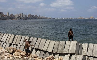Workers prepare to place cement blocks to reinforce the sea wall against rising water levels on the corniche in Alexandria, Egypt, August 8, 2019. (Maya Alleruzzo/AP)