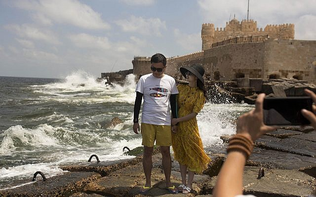 A couple poses for a portrait on cement blocks placed as reinforcement against rising water levels near the citadel in Alexandria, Egypt, August 8, 2019. (Maya Alleruzzo/AP)