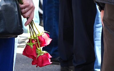 A woman holds roses as she and others gather for the funerals of five Russian nuclear engineers killed by a rocket explosion in Sarov, the closed city located 370 kilometers (230 miles) east of Moscow, which has served as a base for Russia's nuclear weapons program since the late 1940s, on August 12, 2019. (Screenshot taken from footage provided by the Russian State Atomic Energy Corporation ROSATOM press service via AP)