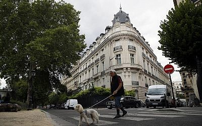 A man walks his dog next to an apartment building owned by Jeffrey Epstein in the 16th district in Paris, August 13, 2019. (AP Photo/Francois Mori)