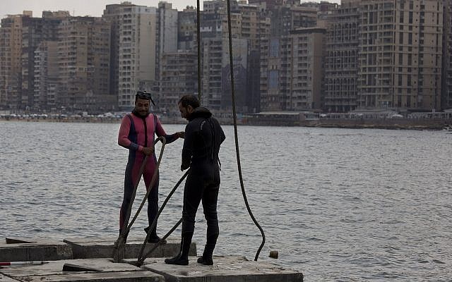 Workers prepare to place cement blocks to stave off rising water levels near the corniche in Alexandria, Egypt,  August 8, 2019. (Maya Alleruzzo/AP)