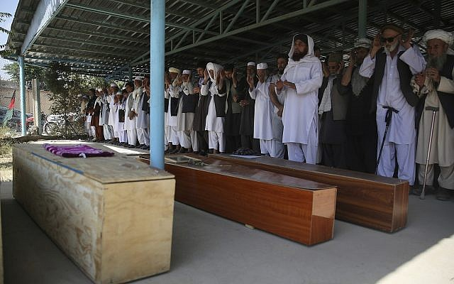 Afghans pray near the coffins of victims of the Dubai City wedding hall bombing during a mass funeral in Kabul, Afghanistan, August 18, 2019. (Rafiq Maqbool/AP)