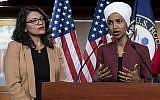In this July 15, 2019, file photo, US Rep. Ilhan Omar, a Minnesota Democrat, right, speaks as US Rep. Rashida Tlaib, a Michigan Democrat, listens during a news conference at the Capitol in Washington. (AP Photo/J. Scott Applewhite, File)
