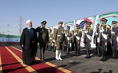 In this photo released by the official website of the office of the Iranian Presidency, President Hassan Rouhani, left, reviews an honor guard as he is accompanied by his Defense Minister Gen. Amir Hatami during a ceremony to unveil Iran-made Bavar-373 air-defense missile system, Iran, Thursday, Aug. 22, 2019. (Iranian Presidency Office via AP)