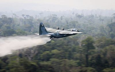In this photo released by Brazil Ministry of Defense, a C-130 Hercules aircraft dumps water to fight fires burning in the Amazon rainforest, in Brazil on August 24, 2019. (Brazil Ministry of Defense via AP)