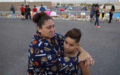 In this August 5, 2019, file photo, Clarissa Hernandez holds Ezra Magallanes as they speak with the media at a makeshift memorial for victims of a mass shooting at a shopping complex in El Paso, Texas. (AP Photo/John Locher, File)
